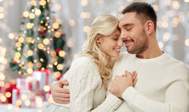 Happy couple over christmas tree lights background Royalty Free Stock Photo