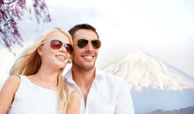 Happy couple over fuji mountain in japan. Summer holidays and dating concept - couple in shades over fuji mountain background stock photography