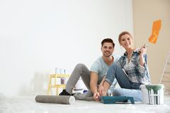 Happy couple with paint planning home repair stock photo