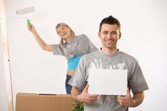 Happy couple painting new house. Together, smiling man holding blank page for copyspace stock photo