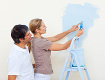 Happy couple painting together. In their new house Royalty Free Stock Photography