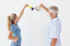 Happy couple painting wall with paintbrushes Stock Image