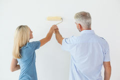 Happy Couple Painting Wall With Roller Stock Photos