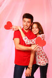 Happy couple with paper hearts on a background of pink tulle Royalty Free Stock Photo