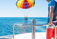 Happy couple Parasailing in Dominicana beach in summer. Couple under parachute hanging mid air. Having fun.  Paradise. Pos Stock Images