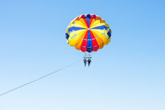 Happy couple Parasailing in Dominicana beach in summer. Couple under parachute hanging mid air. Having fun. Tropical Paradise. Royalty Free Stock Photo