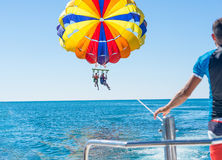 Happy couple Parasailing in Dominicana beach in summer. Couple under parachute hanging mid air. Having fun. Tropical Paradise. Pos Royalty Free Stock Images