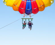 Happy couple Parasailing in Dominicana beach in summer. Couple under parachute hanging mid air. Having fun. Tropical Paradise. Pos stock image