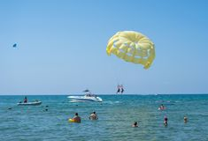 Happy couple Parasailing on Tropical Beach in summer. Couple under parachute hanging mid air. Having fun. Tropical Paradise. Posit royalty free stock images