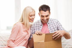 Happy couple with parcel box at home Royalty Free Stock Photo