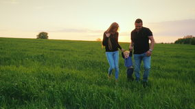 A happy couple of parents with a small son are walking across the field towards the sunset. Happy family with a child