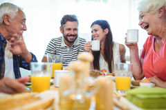 Happy couple and parents talking while having breakfast. At home royalty free stock photography
