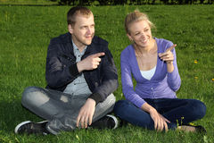Happy couple in park showing something Royalty Free Stock Image