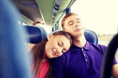 Happy couple or passengers sleeping in travel bus Stock Photo
