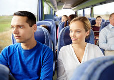 Happy couple or passengers in travel bus. Transport, tourism, road trip and people concept - happy couple with group of happy passengers or tourists in travel Royalty Free Stock Photography