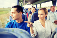 Happy couple or passengers in travel bus. Transport, tourism, road trip and people concept - happy couple with group of happy passengers or tourists in travel Royalty Free Stock Images