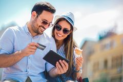 Happy couple paying on line with credit card and digital tablet. On the street royalty free stock photo