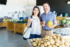 Happy Couple Paying For Their Food At Market stock photos