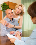 Happy couple of pensioners talking with manager Royalty Free Stock Image