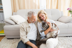 Happy couple with pet cat on floor Stock Images