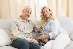 Happy couple with pet cat on sofa Stock Image