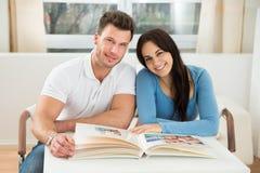 Happy couple with photo album Stock Photography
