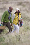 Happy couple with picnic basket holding hands in field Stock Image
