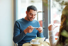 Happy couple picturing food by smartphone at cafe. People, communication and dating concept - happy couple with smartphones picturing food at cafe or restaurant Stock Photo