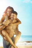 Happy couple piggyback on the beach Stock Photography