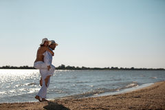 Happy couple piggyback ride on sea shore. Happy young couple dressed in white, on the beach, on a piggy back ride Stock Image