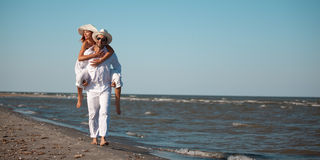 Happy couple piggyback ride on sea shore. Happy young couple dressed in white, on the beach, on a piggy back ride Royalty Free Stock Photography