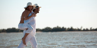 Happy couple piggyback ride on sea shore Stock Photo