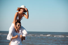 Happy couple piggyback ride on sea shore. Happy young couple dressed in white, on the beach, on a piggy back ride Royalty Free Stock Image