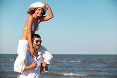 Happy couple piggyback ride on sea shore. Happy young couple dressed in white, on the beach, on a piggy back ride Stock Photo