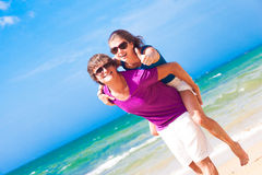 Happy couple piggybacking cheerful on beach thumbs Stock Photography