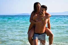 Happy couple piggybacking during summer day at sea. stock images