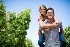 Happy couple piggybacking at vineyard against blue sky Stock Photo