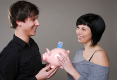Happy couple with piggybank Stock Photos