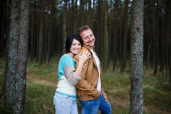 Happy couple in a pine forest Royalty Free Stock Photography