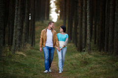 Happy couple in a pine forest Royalty Free Stock Image