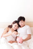 Happy couple with pink piggy bank Stock Photography