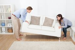 Happy couple placing sofa in living room. Full length of happy couple placing sofa in living room of new home royalty free stock image
