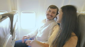 Happy couple in the plane shows a thumbs up. Pretty girl and handsome guy are sitting on the passenger`s seats in the plane. Bearded man holds hands with his stock video