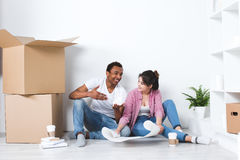 Happy couple planning decoration at new home sitting on the floor. Stock Photos