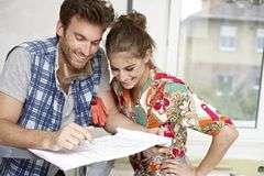Happy couple planning a new home. Happy young couple planning new home, DIY stock photo