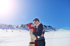 Happy couple playful together during winter holidays vacation outside in snow park Royalty Free Stock Images