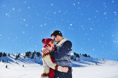 Happy couple playful together during winter holidays vacation outside in snow park Royalty Free Stock Image
