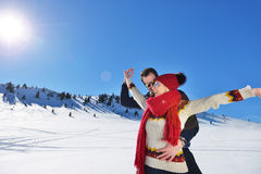 Happy couple playful together during winter holidays vacation outside in snow park Stock Image