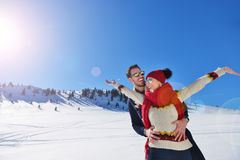 Happy couple playful together during winter holidays vacation outside in snow park Stock Photos
