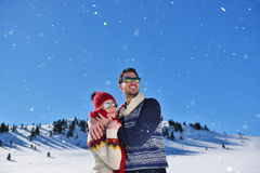 Happy couple playful together during winter holidays vacation outside in snow park Royalty Free Stock Photography